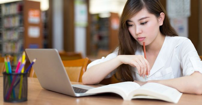 college student studying in library - Tips For Better Studying